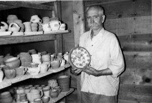 Ebring in his tudio displaying his glazed work prior to firing n.d.