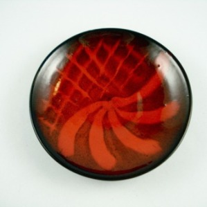 "Ernst & Alma Lorenzen plate. Signature. Nova Scotia. Deep oxblood red coloured, with red feathered and latticed design over black interior. Red Clay. 7 ¼"" diameter, 1 ½"" high"