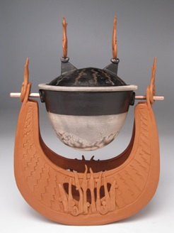 Carol Smeraldo . 2009. Learned Boat: Percolating Impressions. Wheel thrown, hand built, sculpted, carved, inlayed, twice burnished terra sigillatta. Lantz clay, black and white naked raku slip resist lidded container, with a large marble inside, suspended on a copper rod. 30.5 h x 20.5 l x 15 w cm.