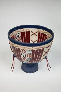 Blue and Red Footed Bowl with Ladders, 1996. Porcelain, slip cast, coloured underglazes, transparent glaze, leather, copper wire, beads, fired to Cone 9 in oxidation. 12.5X13.5cm. Photo: Chris Myhr