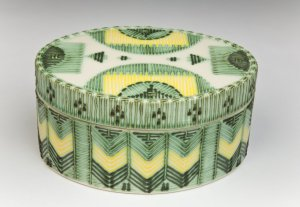 "Green and yellow oval ""quillwork"" covered box, 1987. White stoneware, press molded, coloured underglazes and slips, transparent glaze, fired to Cone 5. 8X17cm. Photo: Chris Myhr"