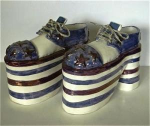 Yonge Street Shoes, 1975, 26 cm long x 17 cm High, porcelain, C/6, Glaze and lustres. Courtesy of the artist.