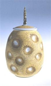 Campbell covered jar, 1984. Thrown and altered, airbrushed stain, glazed interior, no glaze on out side except on the stem. Over fired creating a pebble surface, C/6, gold lustre. Courtesy of the artist.
