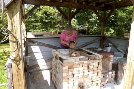 Judy Blake loading sawdust around a saggared pot for firing.