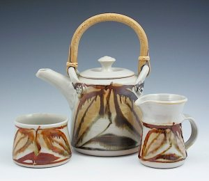 Robin Hopper. 4 - 6 cup teapot, cream and sugar -2005. Gas reduction fired porcelain, over glaze decoration in the majolica style. Cone 10. Teapot 22.9cm.