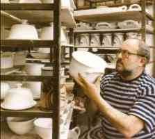 Robin Hopper in his studio with shelves of his functional ware