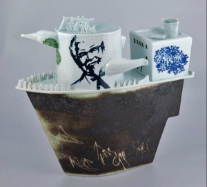 Harlan House. Invasion Of Western Fast Food To Rural China. 2009. Collage of slip cast porcelain parts and some hand built parts. Cobalt brush drawing under glaze, and Chinese cobalt transfer decals underglaze with clear HH celadon over. Hull has Marine Wudi sinter with sgraffiti in it. 47 x 49.5 x 20 cm.