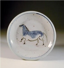 "Barbara Tipton. 2004. Horse plate, wheel thrown white stoneware, approximately 15 cm across, brush decorated greenware with dilute cobalt/manganese wash and a more saturated line, iron brush ""spatters"", fired in a gas kiln to cone 8-9,."