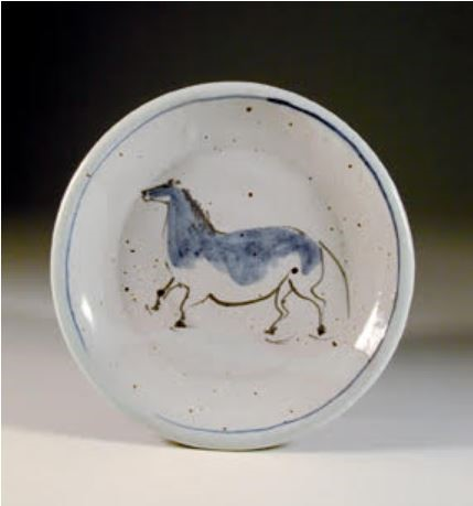 """Barbara Tipton. 2004. Horse plate, wheel thrown white stoneware, approximately 15 cm across, brush decorated greenware with dilute cobalt/manganese wash and a more saturated line, iron brush """"spatters"""", fired in a gas kiln to cone 8-9,."""