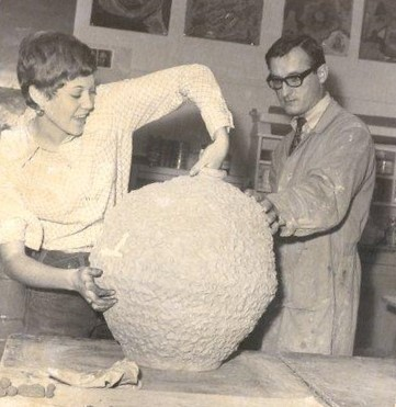 Teacher Victor Cicansky looks on as Diana Dobson examines her freshly fired vase.
